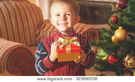 Closeup Toned Portrait Of Happy Smiling Little Boy Holding Box With Christmas Gift Or Present And Lo