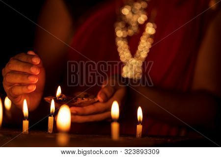 Indian Housewife Or Newly Bride Woman Wearing Traditional Red Saree & Gold Jewelry Lighting Candles