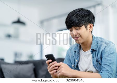 Happy Asian Teenager Using Smart Phone And Smiling On Sofa Living Room At Home. Asian Man Holding An