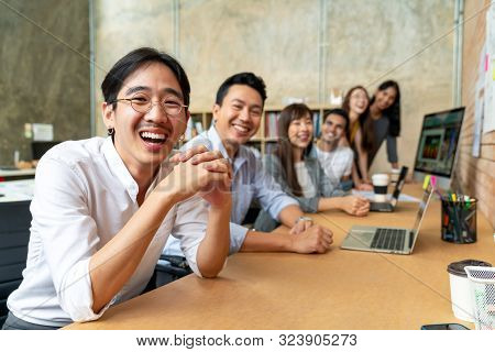 Happy Asian Man And Creative Team Are Smiling And Looking At Camera In Modern Workspace Office. Happ