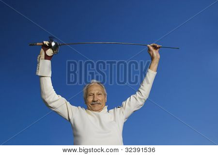 Senior male fencer holding epee above head
