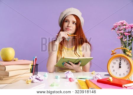 Photo of perplexed student girl writing in exercise book while doing homework isolated over purple background poster
