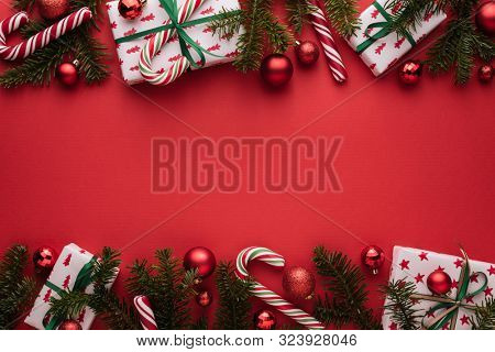 Red Christmas and New Year background. Decorative border of fir branches, gift boxes, Christmas balls and candy cane. Copy space for Christmas creep