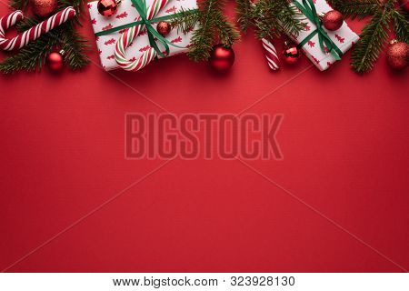 Red Christmas and New Year background. Decorative border of fir branches, gifts, Christmas balls and candy cane. Copy space for Christmas creep