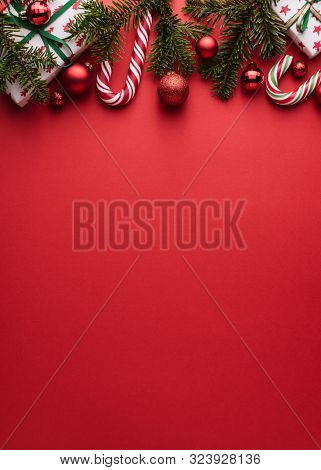 Red background Copy space for Christmas creep. Border of fir branches, gifts, Christmas balls and candy cane
