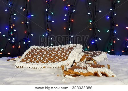 The crashed hand-made eatable gingerbread house, snow decoration, garland background illumination poster