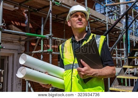Male builder foreman, worker, surveyor, engineer or architect on construction site holding building plans and clipboard