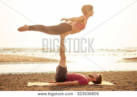 Two Young Man And Beautiful Woman On Beach Doing Fitness Yoga Exercise Together. Acroyoga Element Fo