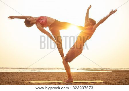 Two People Practicing Yoga In The Sunset Light On Goa India Beach. Female And Male Acro Yogi Tantra