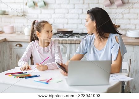 Prioritizing concept. Busy mother giving attention to her daughter while working on laptop at home poster