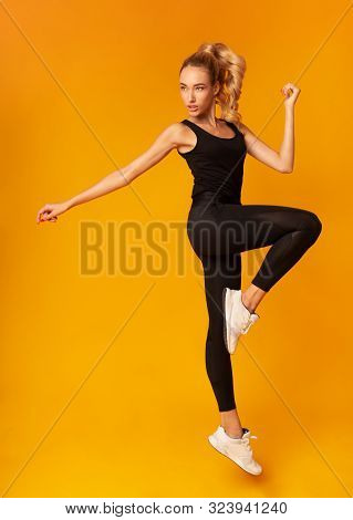 Fit Young Woman Exercising Jumping In Studio Over Yellow Background. Workout Concept. Vertical, Full