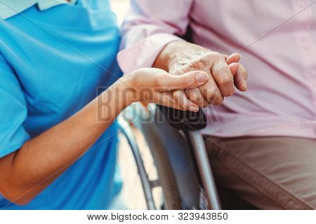 Nurse consoling a senior woman in the nursing home holding her hand in the nursing home