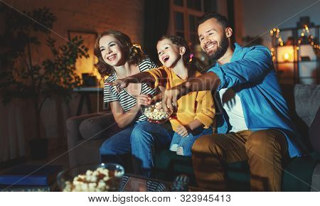Family Mother Father And Child Daughter Watching Projector, Tv, Movies With Popcorn In The Evening