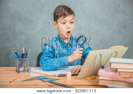 Inquisitive Little Boy Is Looking Through Magnifying Glass At Something In His Book Like Detective.