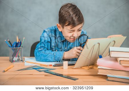 Inquisitive little boy is looking through magnifying glass at something in his book like detective. poster