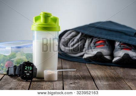 Preparation For Going To The Gym. A Bag With Sneakers And Pants, Shaker With Protein Cocktail, Sport