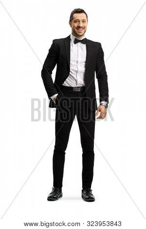 Full length portrait of an elegant young man in a suit and bow tie posing with hand in pocket isolated on white background