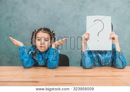 Schoolchildren sitting at the desk. Boy is hiding behind the sheet of paper with exclamation mark. Girl is throwing her hands, looking with puzzled face expression. poster