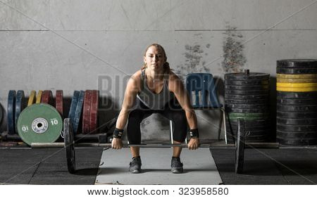 Strong female weight lifter preparing for lift in grungy gym.