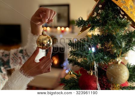 Hands of a mixed race woman in her sitting room at Christmas, holding a gold bauble and decorating Christmas tree