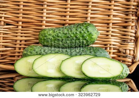 Group Of Two Whole Four Slices Of Meaty Fresh Pickling Cucumber With Braided Rattan Behind