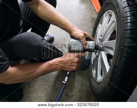 Removing Car Mechanic To Repair The Leaky Tire Car Wheels.mechanic Changing A Car Tire On A Vehicle