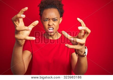 Young beautiful african american woman with afro hair over isolated red background Shouting frustrated with rage, hands trying to strangle, yelling mad