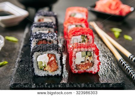 Macro photo of maki sushi roll with rice, cream cheese, salmon, eel, cucumber, flying fish caviar. Nori maki rolls with raw trout, red and black tobiko on natural dark stone background close up