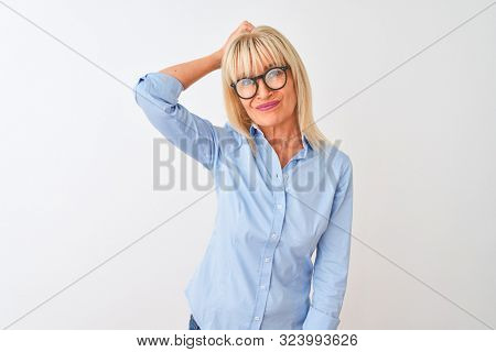Middle age businesswoman wearing elegant shirt and glasses over isolated white background confuse and wondering about question. Uncertain with doubt, thinking with hand on head. Pensive concept.