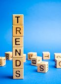 Wooden blocks with the word Trends. Popular and relevant topics. New ideological trends. Recent and latest trend. poster