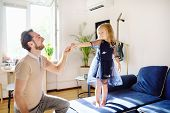 Young handsome father with his little curly hair daughter dancing at home. Loving dad and his preschooler girl playing together at home. Happy fatherhood poster