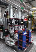 Interior of independent modern gas boiler room with manometers valves pumps and thermo-insulation on pipelines poster