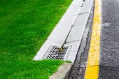 drainage system edge tray with concrete grate for rainwater drainage into the sewer on a road side after rain, close up nobody. poster