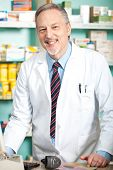 Mature pharmacist in his store smiling poster