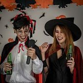 Group of young adult and teenager people celebrating a Halloween party carnival Festival in Halloween costumes drinking alcohol beer poster