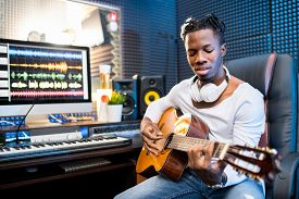 Contemporary young musician or guitarist in casualwear playing guitar while sitting in sound recording studio
