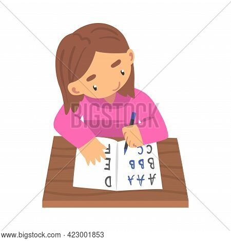 Lovely Girl Learning To Write, Elementary School Student Sitting At Desk And Writing Letters In Note