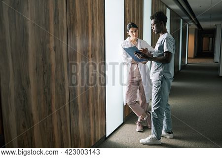 Full Length Portrait Of Young African-american Medic Talking To Female Colleague In Clinic