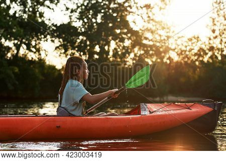 Side View Of Young Woman Looking Relaxed While Kayaking In A Lake Surrounded By Nature On A Late Sum
