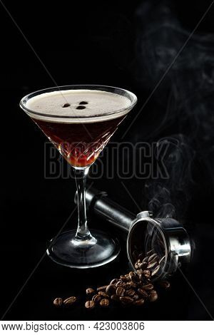 Alcohol cocktail Espresso Martini cocktails garnished with coffee beans, beans in espresso holder in smoke and on black background. Copy Space.