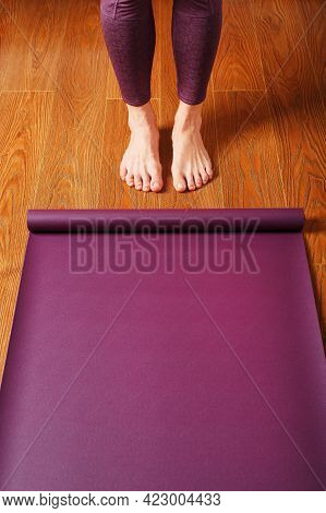 The Girl's Feet Stand In Front Of An Unfolded Yoga Mat On The Wooden Floor.