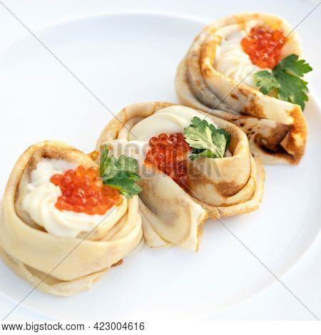 Expensive Thin Pancakes Decorated With Cream And Red Caviar. Portion Of Pancakes On Plate. Delicate