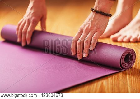 A Woman's Hands Lay Out A Lilac Yoga Or Fitness Mat Before A Workout Practice At Home On A Wooden Fl