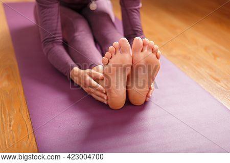 Girl Practicing Yoga Leaning Forward Sitting, Feet Forward-paschimottanasana Pose