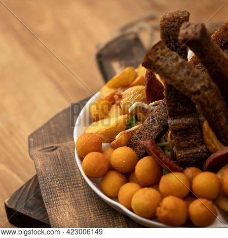 Beer Snack. Close Up Of Potato Croquettes, Black Bread Croutons And Fried Potatoes On Blurred Wooden