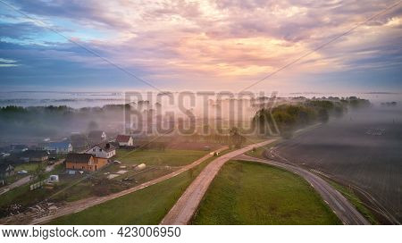 Aerial View Of Village, Rural Dirt Road And Trees Covered By Fog. Early Misty Morning Sunrise Panora