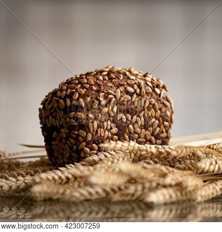 Loaf Of Rye Bread With Sunflower Seeds On Kitchen Table With Wheat Ears. Whole Grain Crispbread Just