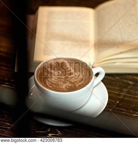 Reading And Coffee. Cup Of Chocolate Cappuccino With Froth And Open Book On Wooden Table. Shot Throu
