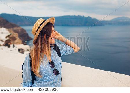 Tourist Woman Walking On Santorini Island, Greece Enjoying Sea And City Landscape. Traveler With Bac