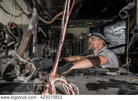 Caucasian Mechanic Inside Rv Coach Bus Diesel Engine Compartment. Replacing Whole Engine Of The Vehi